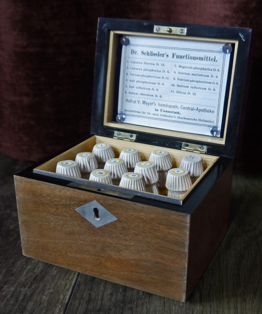 Bild: Kiste mit 11 Schüssler-Salzen von 1923 von DeepSilent63 – Eigenes Werk [CC BY-SA 4.0], via Wikimedia Commons